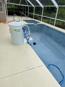 A Pool Cleaner next to a pool, as seen by Clear Solutions Pool Service